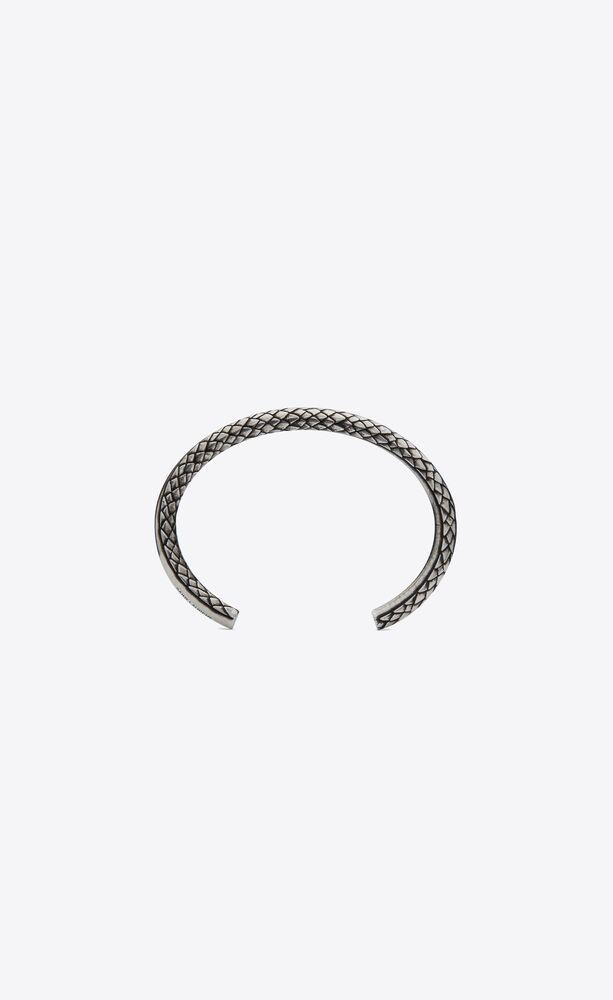 kleiner, schlangenartig gewundener armreif aus metall